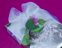 Silver-and-pink blossom paper with white ribbon and faux blossoms