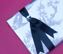 Silver blossom-and-bird paper with black ribbon and jewel