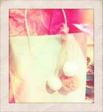 White gift bag with pink tissue paper and pom-poms