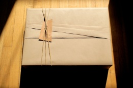 Japanese-inspired folded kraft paper wrapping with leather and veneer detail