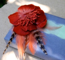 Gift wrapped in handmade paper with orange flower/feather broach