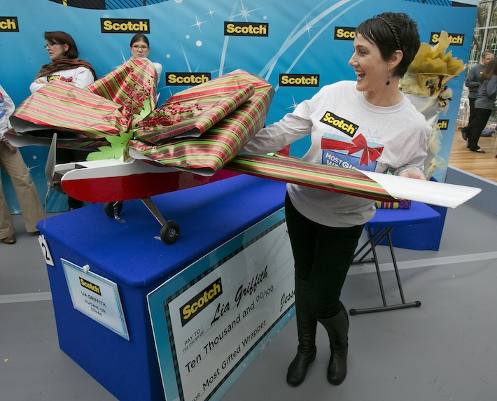 Lia Griffith with wrapped model airplane as she wins Most Gifted Wrapper Contest in New York